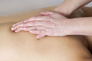 Photo of a male back massage using reinforced kneading stroke